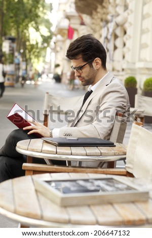 Modern businessman sitting at coffee shop and making financial plan. Small business.  - stock photo