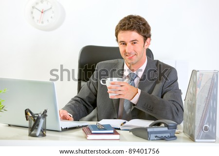Modern businessman sitting at office desk and having coffee