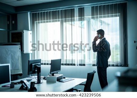 Modern businessman talking on a mobile phone while looking through the window. - stock photo