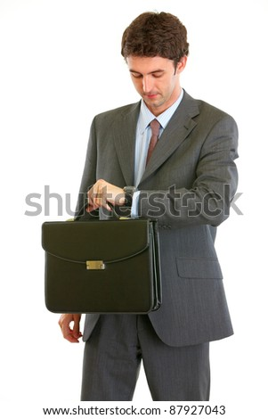 Modern businessman with briefcase checking time  isolated on white