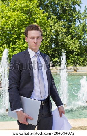 Modern businessman with laptop and papers - stock photo