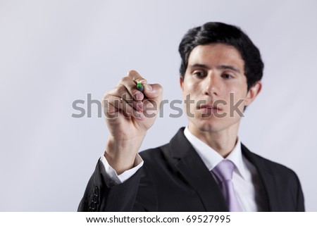 Modern businessman writing on the whiteboard (selective focus) - stock photo