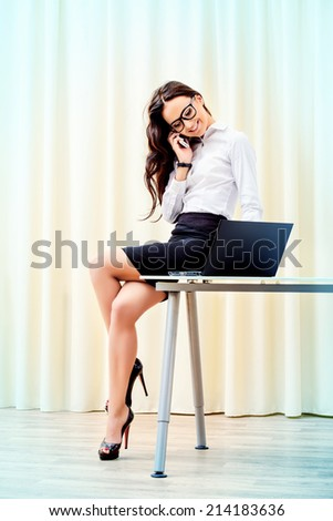Modern businesswoman talking on her cellphone in the office. - stock photo