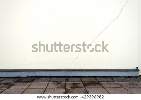 Modern but cracked white plaster street wall background, example of bad construction - stock photo