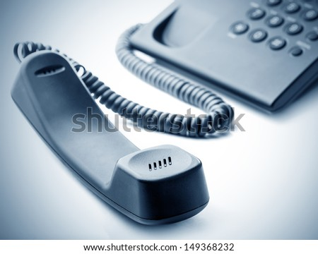 Modern call phone with cord in office - stock photo