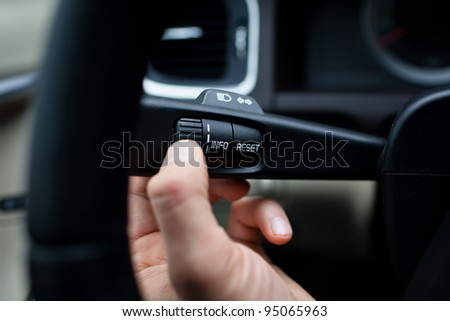Modern car interior - driver pressing a button, using the car computer - stock photo