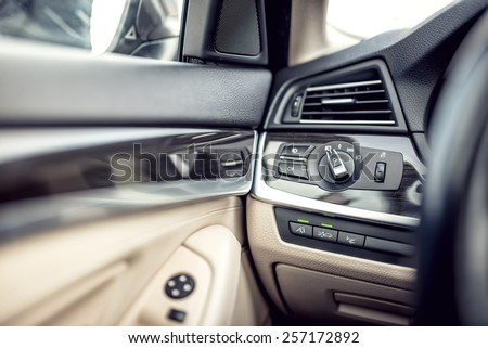 Modern car interior with leather and premium details. Headlights adjustment control and cockpit details - stock photo