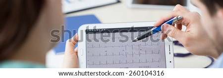 Modern cardiologists analyzing patient's electrocardiogram on tablet - stock photo