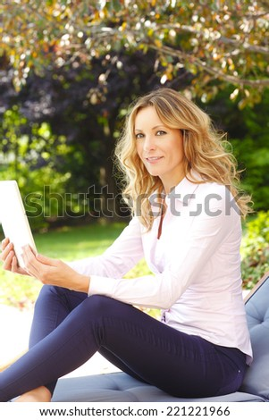 Modern casual woman working at home while using digital tablet.  - stock photo