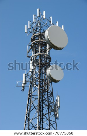 Modern cell and antenna with flat parabola on blue sky - stock photo