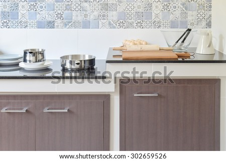 modern ceramic kitchenware and utensils on the black granite counter top - stock photo