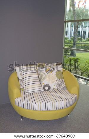 Modern chair within sparsely furnished room with brightly colored scatter cushions - stock photo