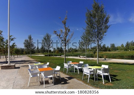modern chairs and tables in a garden with boil - stock photo