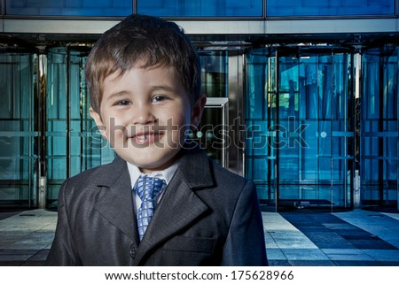 Modern child dressed businessman with hands in his tie and skyscrapers in the background - stock photo