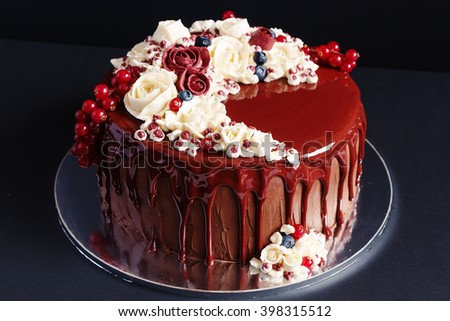 Modern chocolate european cake decorated with flowing glaze and buttercream flowers. Black background. Shallow focus
