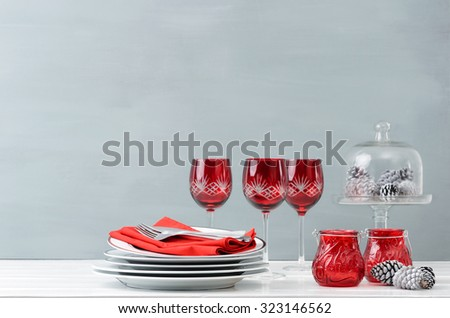 Modern christmas decoration table display with crockery and festive holiday red wine glasses - stock photo