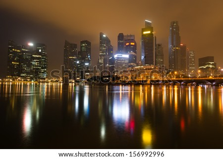 Modern city skyline of business district downtown in night with yellow glow