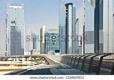 Modern cityscape - Dubai downtown. Subway train approaching to a station. - stock photo