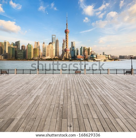 modern cityscape in shanghai,city skyline with wooden floor and railing on the waterfront  - stock photo