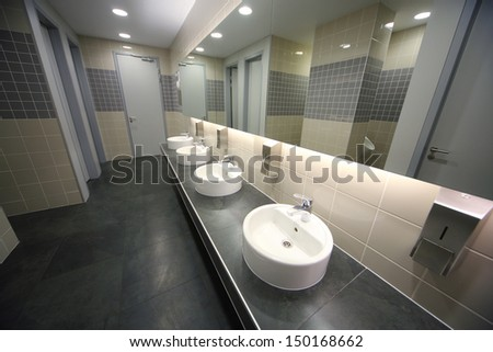 Modern clean toilet decorated with tiles with four sinks - stock photo