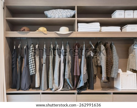 modern closet with row of dress hanging on coat hanger in wardrobe. - stock photo