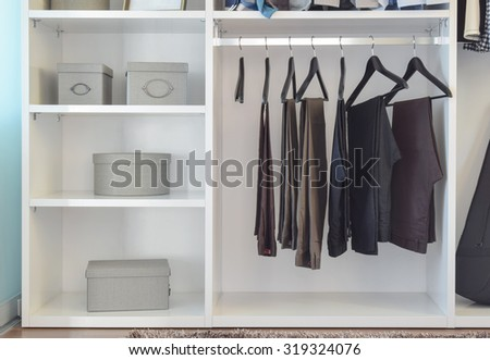 modern closet with row of pants hanging in white wardrobe - stock photo