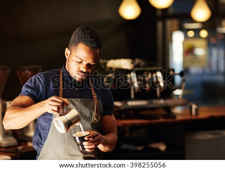 Modern coffee shop with African barista pouring milk into cappuc - stock photo