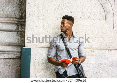 Modern College Student in New York. Wearing gray shirt, wristwatch, carrying shoulder leather bag, an African American guy standing by wall on street, listening music with earphone, reading red book.  - stock photo