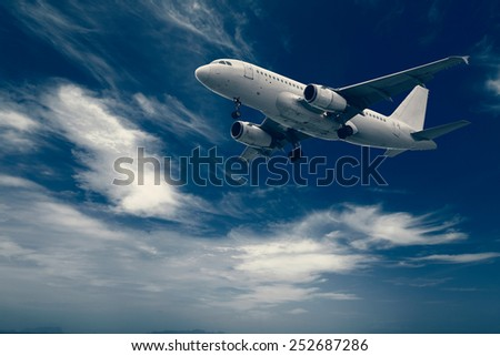 Modern commercial airliner flying high altitude above clouds