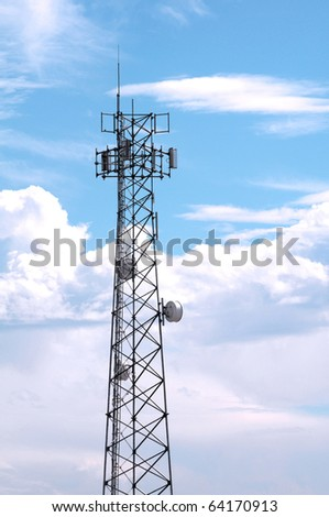 Modern communication tower against a blue cloudy sky. - stock photo