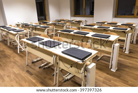 Modern computer classroom with laptop computers, tables and chairs. - stock photo