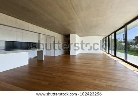 modern concrete house with hardwood floor, wide open space - stock photo