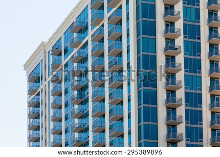 Modern Condo Tower under clear blue sky - stock photo