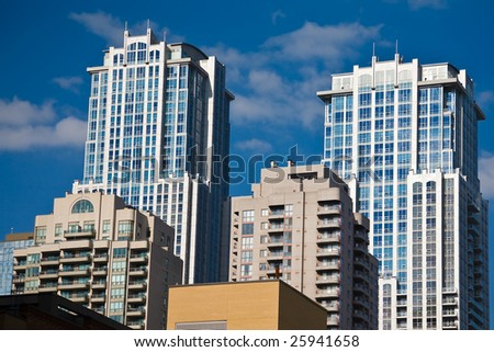 Modern condominiums against bright blue sky