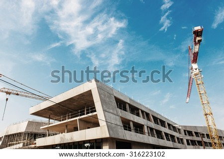Modern construction site with cranes against blue sky - stock photo