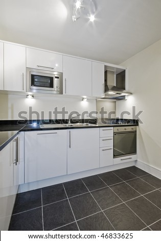modern contemporary kitchen in white with black stone worktop - stock photo