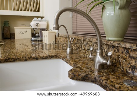 Modern contemporary kitchen interior with granite worktop and cream units, focus on the sink area. - stock photo