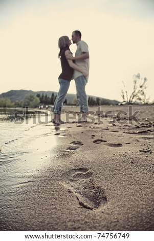 modern couple holding each other on beach with footprints in sand - stock photo