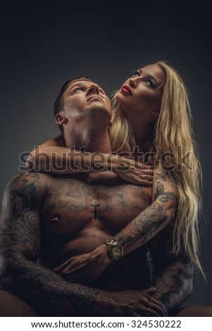Modern couple of shirtless tattooed man and sexy blond woman in bra. Isolated on grey background. - stock photo