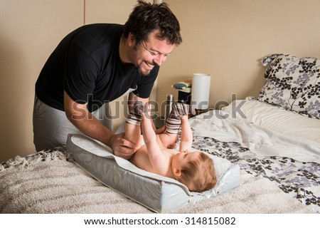 Modern dad changing diapers - stock photo