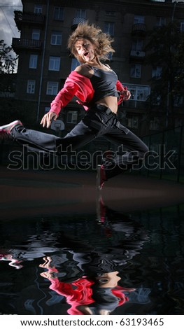 Modern dancer jumping in city - stock photo