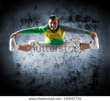 Modern dancer jumping over the dramatic background - stock photo