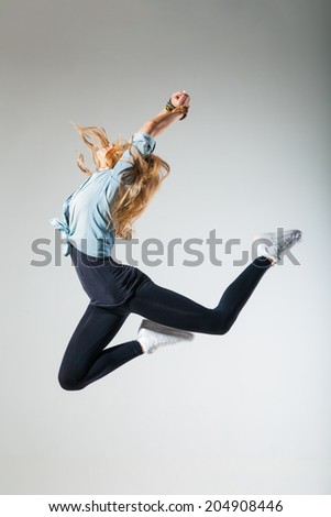 Modern dancer poses in front of gray studio background - stock photo