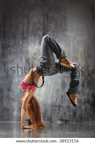 modern dancer poses in front of the gray wall