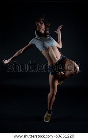 Modern dancer poses on black background - stock photo