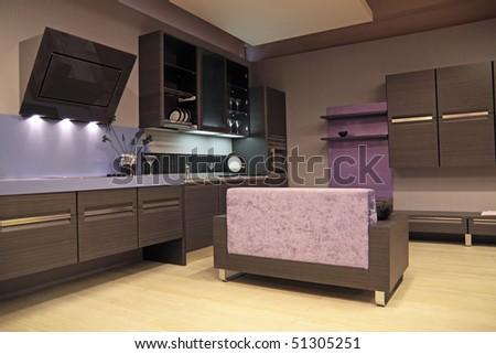 Modern dark brown kitchen with a sofa - stock photo