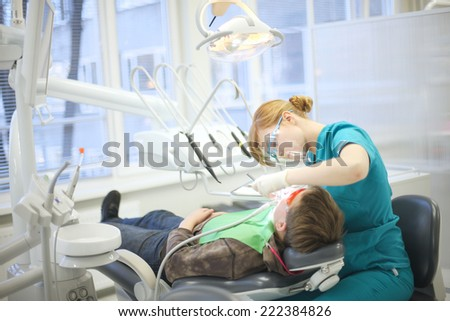Modern dental clinic, young dentist working - stock photo