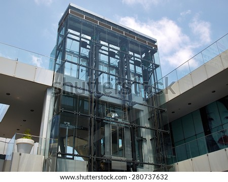 Modern design transparent glass elevator in an office building - stock photo