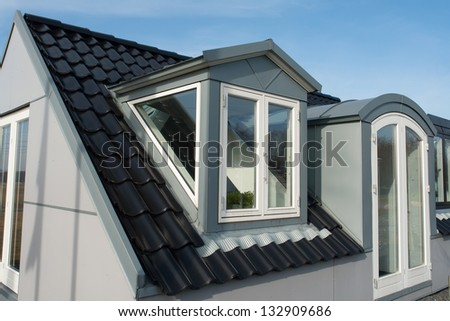 Modern design vertical roof water proof windows with black tiles - stock photo