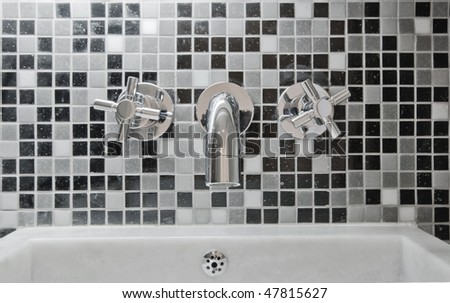 modern designer chrome water mixer tap on  mosaic tile wall - stock photo